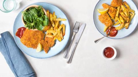 Cornflakes-Schnitzel mit gebackenen Pommes und Nüsslisalat