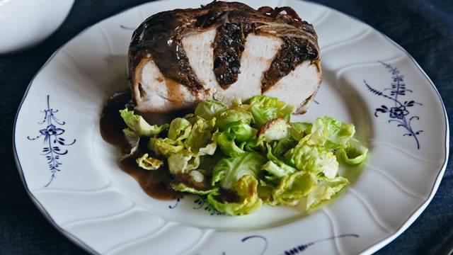 Schweinebraten im Speckmantel gefüllt mit Trockenpflaumen serviert mit gebratenem Rosenkohl