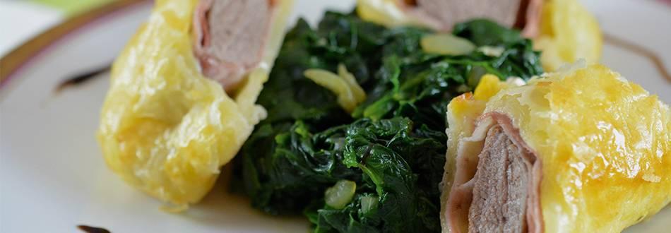 Lammfilet mit Prosciutto crudo im Blätterteig, serviert auf Blattspinat